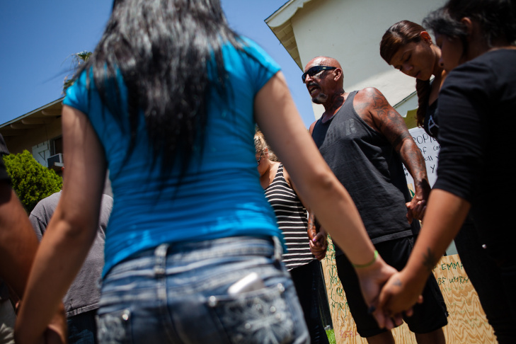 Pastor Phil Aguilar of Set Free Church in Anaheim, leads friends of Manuel Diaz in prayer at the site of the youth's death.