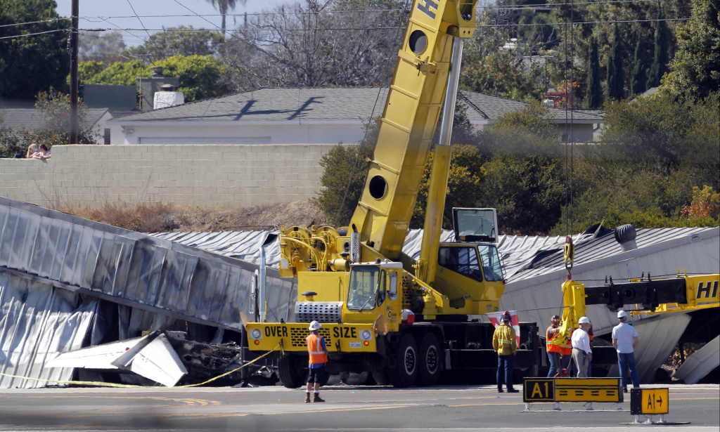 Two cranes are set in position to lift the wrecked hangar buildings off the remains of a crashed jet plane, before investigators try to retrieve remains and the jet's cockpit voice recorder at the airport in Santa Monica, Calif., on Monday, Sept. 30, 2013. A lawsuit against the estate of the pilot, who died in the crash, has been filed on behalf of the family of one of the passengers who were killed.