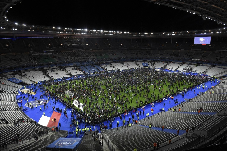 Spectators gather on the pitch of the Stade de France stadium following the friendly football match between France and Germany in Saint-Denis, north of Paris, on November 13, 2015, after a series of gun attacks occurred across Paris as well as explosions outside the national stadium where France was hosting Germany. At least 18 people were killed, with at least 15 people killed at the Bataclan concert hall in central Paris, only around 200 metres from the former offices of Charlie Hebdo which were attacked by jihadists in January.  AFP PHOTO / FRANCK FIFE        (Photo credit should read FRANCK FIFE/AFP/Getty Images)