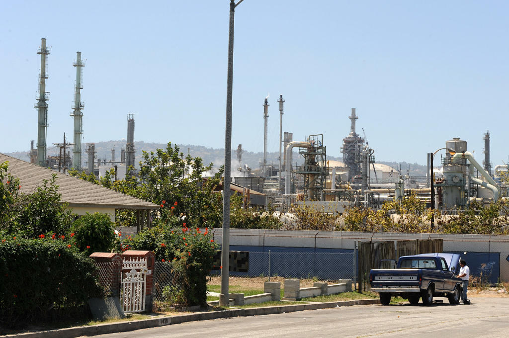 A man works on his car in front of his home which is located near an oil refinery (background) in Wilmington, California on August 9, 2008.
