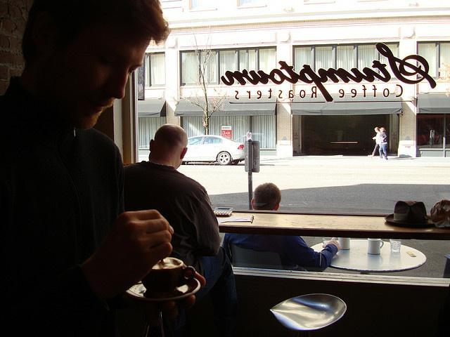 A man drinks coffee from Stumptown Coffee Roasters.