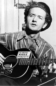 Woody Guthrie seen playing his guitar with the signature