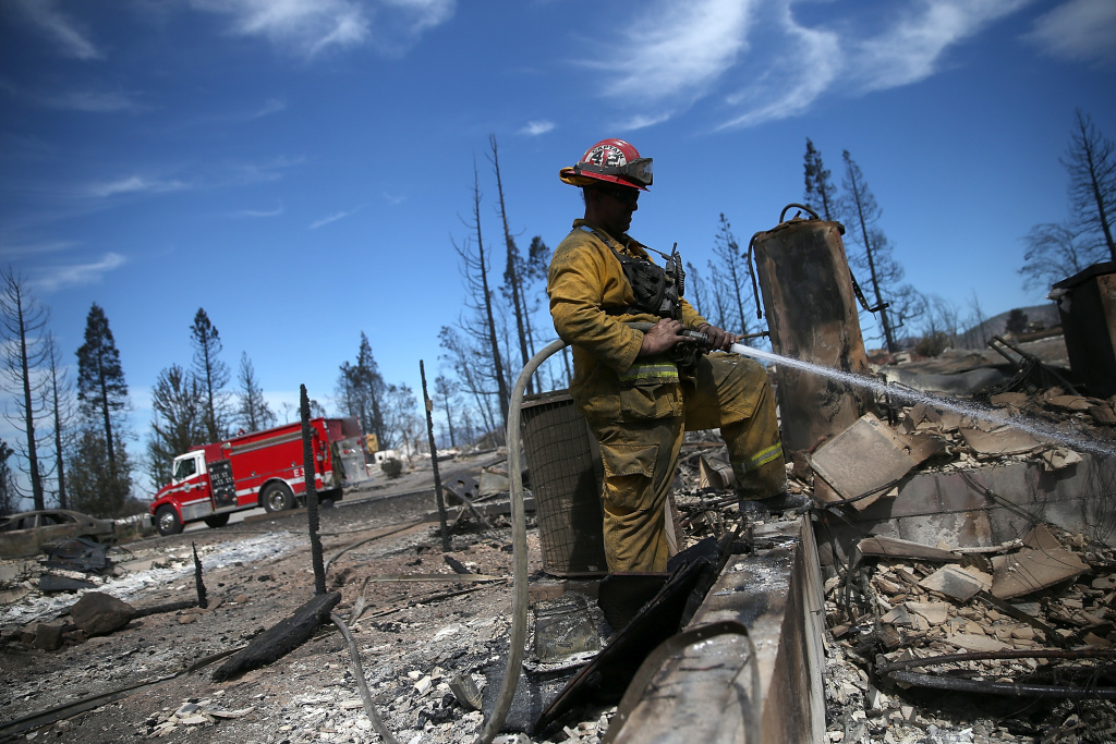 A firefighter cools off hot spots in the remains of a destroyed home on September 16, 2014 in Weed, California. Fueled by high winds, a fast-moving wildfire swept through the town of Weed yesterday afternoon, burning 100 structures that included the high school and a lumber mill.