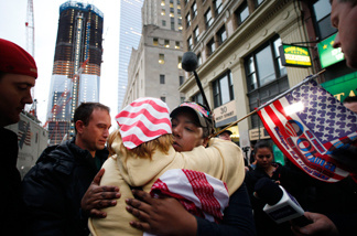 Dionne Layne, facing camera, hugs Mary Power as they react to the news of the death of Osama bin Laden, Monday, May 2, 2011 in New York. At left is the rising tower, 1 World Trade Center, also known as the Freedom Tower.