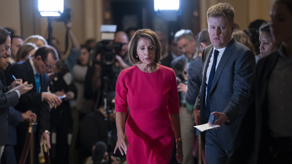 Speaker of the House Nancy Pelosi, D-Calif., departs a news conference with Drew Hammill, a member of her senior staff, after reiterating her opposition to funding the president's border wall.