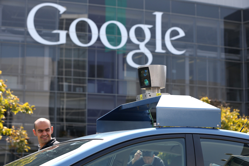 MOUNTAIN VIEW, CA - SEPTEMBER 25:  People look at camera on top of a Google self-driving car at the Google headquarters on September 25, 2012 in Mountain View, California.