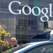 People look at camera on top of a Google self-driving car at the Google headquarters on September 25, 2012 in Mountain View, California.