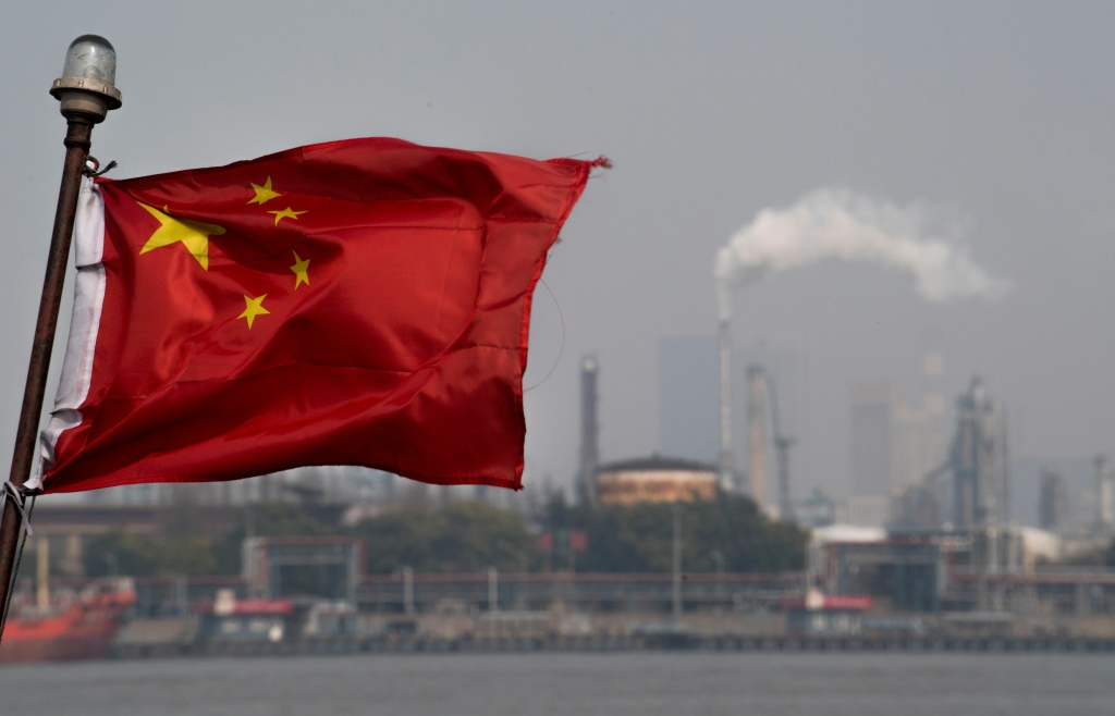 A Chinese flag flutters in front of the Shanghai Gaoqiao Company Refinery in Shanghai on March 22, 2018.
