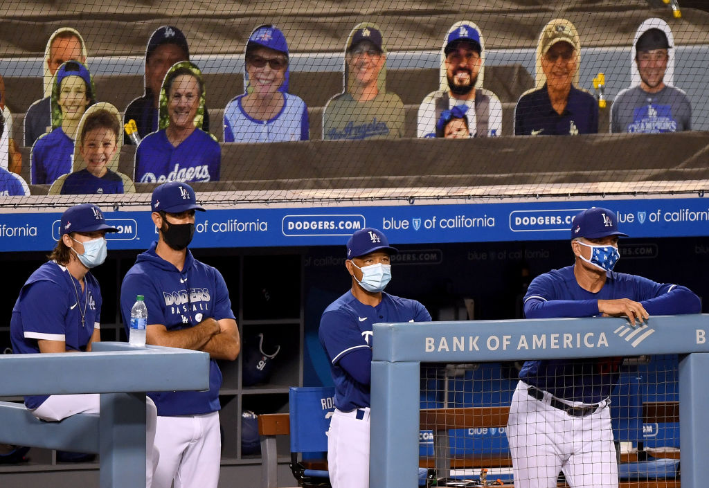 Bob Geren #8, Manager Dave Roberts #30, Mark Prior #23 and Danny Lehmann watch the final out of the game in front of cutout fan faces, in 12-2 preseason win over the Arizona Diamondbacks during the coronavirus (COVID-19) pandemic at Dodger Stadium on July 20, 2020 in Los Angeles, California.