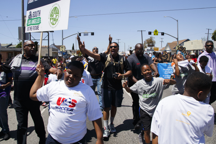 LOS ANGELES, CA - APRIL 29: Participants of a peace rally at the intersection of Florence and Normandie, hold hands and pray before marching on the 25th anniversary of the LA riots, on April 29, 2017 in Los Angeles, California. Florence and Normandie was the flashpoint for the riots that was sparked by the police acquittals in the Rodney King beating. (Photo by Warrick Page/Getty Images)