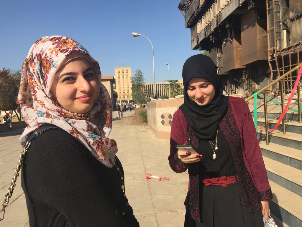 Sisters Raffal, left, and Farah Khaled are first-year students at Mosul University in Iraq. They're standing outside the university library, which was burned down, along with most of its books, by ISIS when it controlled the city.