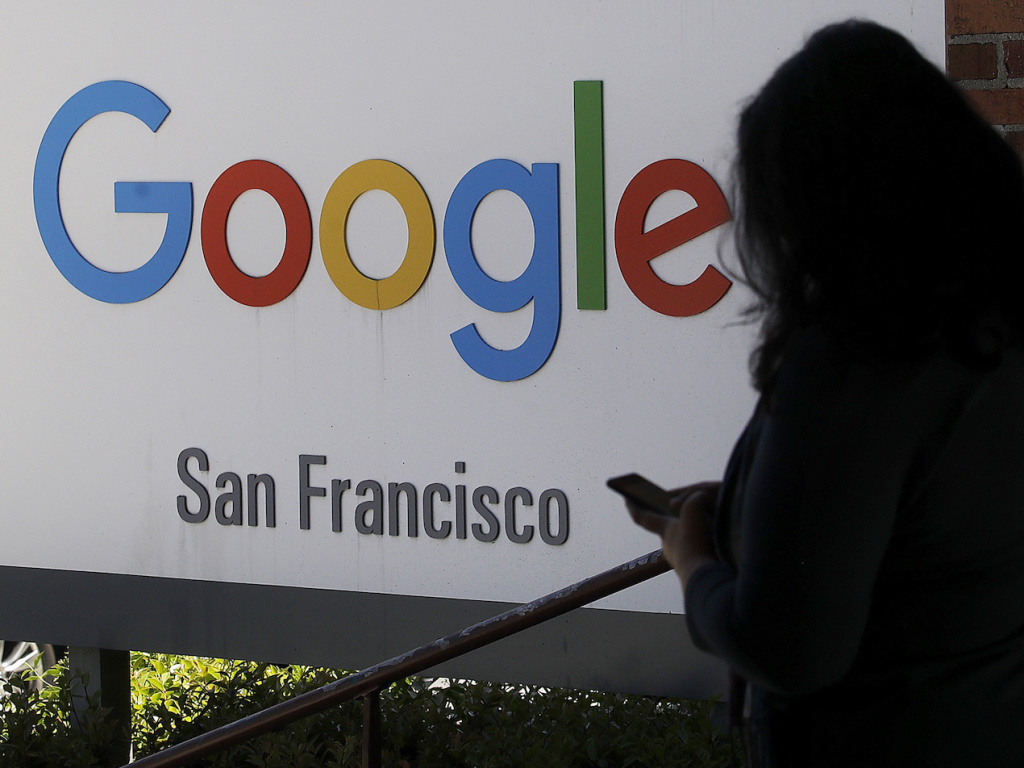 A woman walks past a Google sign in San Francisco. The Justice Department is launching an antitrust review of major online companies. The DOJ did not name the firms, but there have been increasing calls to regulate companies like Google, Facebook and Amazo