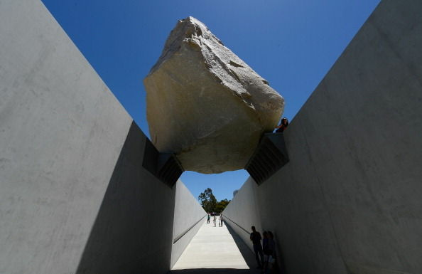 Visitors walk underneath the ''Levitated Mass.'' The exhibit was created by artist Michael Heizer, which features a 340-ton megalith rock.