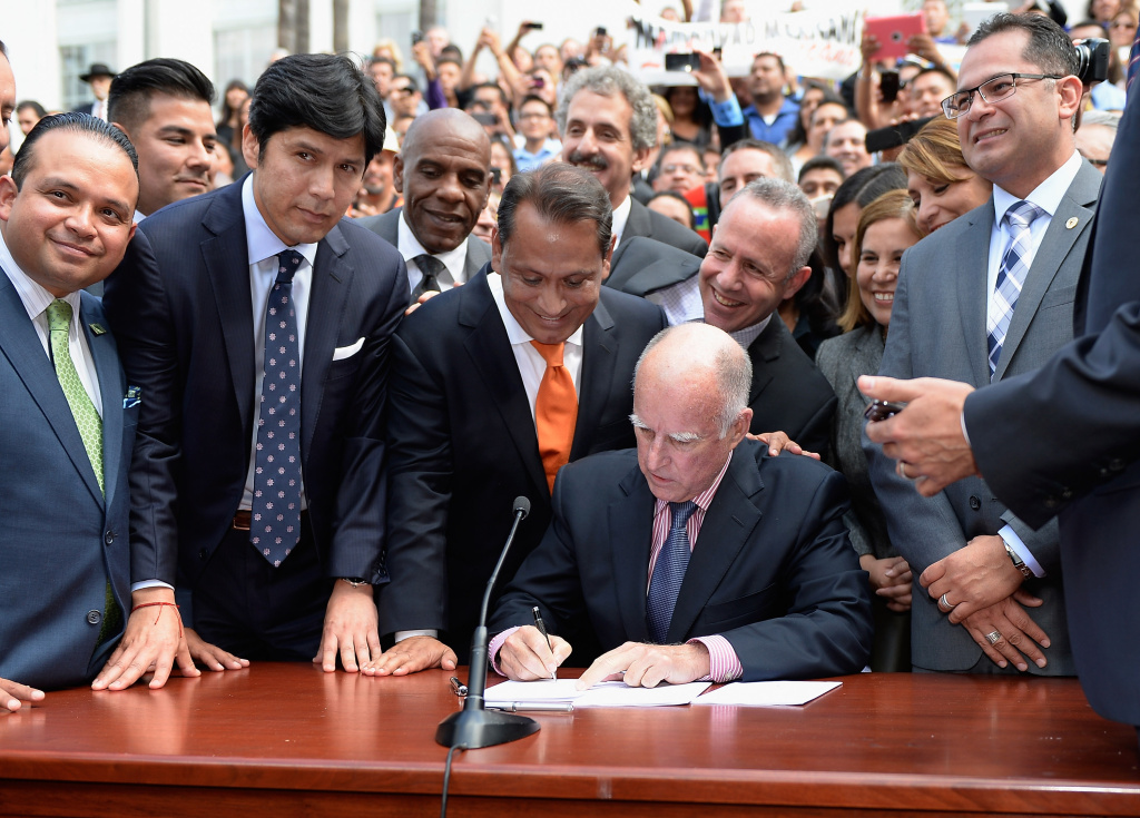 California Governor Jerry Brown (C) signs bill AB60 as Democratic State Senator Kevin de Leon (2nd L), state assemblyman Luis Alejo (L) and councilman Gil Cedillo (3rd L) watch on the steps of Los Angeles City Hall  October 3, 2013 in Los Angeles, California. California Assembly Bill 60 also known as the Safe and Responsible Driver Act allows illegal immigrants to receive a permit to legally drive in California.