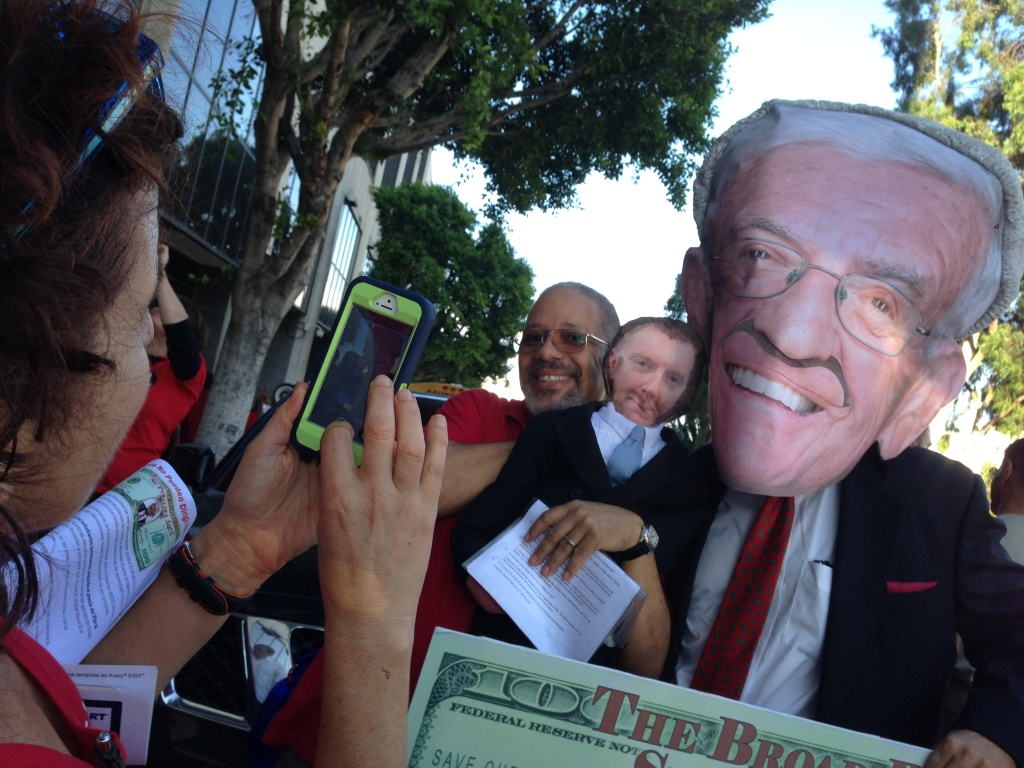 L.A. Unified teacher Elgin Scott holds a likeness of former superintendent John Deasy at a teachers union rally protesting what they say is the influence of billionaire Eli Broad in the school district's superintendent search.
