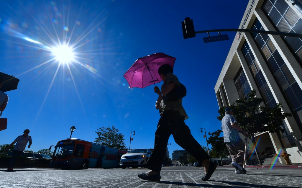 File: A pedestrian uses an umbrella on a hot sunny morning in Los Angeles October 24, 2017 amid a late season heatwave hitting southern California.
