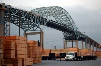 A truck loads up with imported lumber near Long Beach's Gerald Desmond Bridge on March 29, 2002. A new $1 billion project will replace the now 42-year-old bridge. It is expected to rise alongside the existing one and be ready for traffic in six years.
