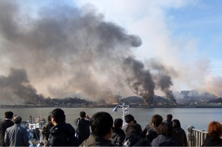 This picture taken by a South Korean tourist shows huge plumes of smoke rising from Yeonpyeong island in the disputed waters of the Yellow Sea on November 23, 2010. North Korea fired dozens of artillery shells onto a South Korean island killing two people, setting homes ablaze, and triggering an exchange of fire as the South's military went on top alert.