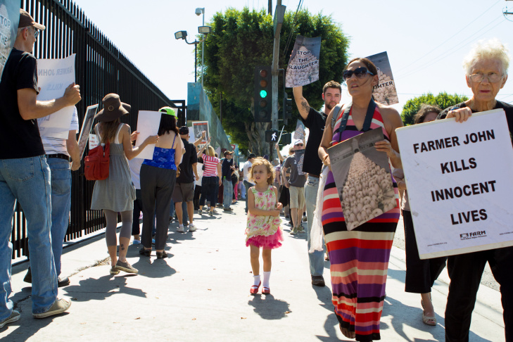 Protestors opposed to the killing of pigs walk past the gates of Clougherty Packing LLC, a meat packing plant for Farmer John in Los Angeles, Calif., Tuesday, October 02, 2012. More than 100 animal rights activists gathered and two arrests were made before the protest.