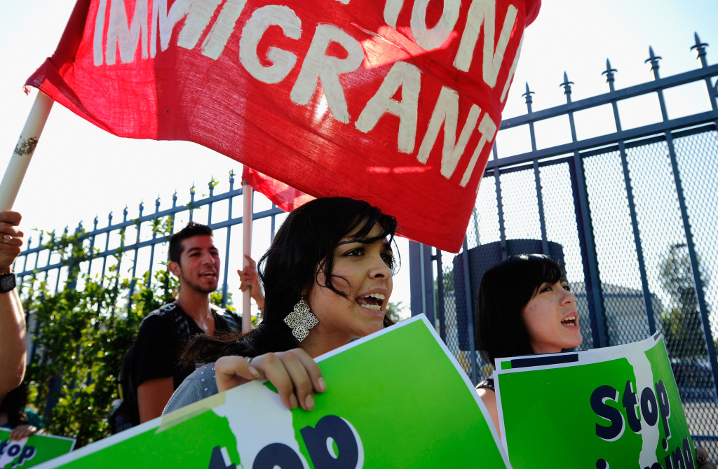 Protesters with Coalition for Humane Immigrant Rights of Los Angeles (CHIRLA) hold signs as they march during an anti Secure Communities program demonstration on August 15, 2011 in Los Angeles, California.