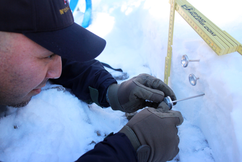 Nathan Judy records the temperatures within each layer of snow.