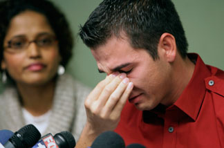 Adult film actor Derrick Burts, 24, who tested positive for HIV, reacts during a news conference, Wednesday, Dec. 8, 2010, in Los Angeles. Burts said he wished he had known more about the risks of contracting sexually transmitted diseases in the industry and is calling for mandatory condom use in porn films. At left is Dr. Shilpa Sayana.