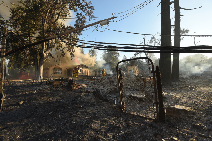 Firefighters battle flames as a house burns in Lower Lake, Calif., on Aug. 14, 2016. The fire reached Main Street in Lower Lake, a town of about 1,200 about 90 miles north of San Francisco, and burned the post office, a winery, a Habitat for Humanity office and several businesses as thick, black smoke loomed over the four-block strip. The fire was creating its own weather pattern and shifted northward into Lower Lake in the afternoon, said Suzie Blankenship, a spokeswoman for the California Department of Forestry and Fire Protection.