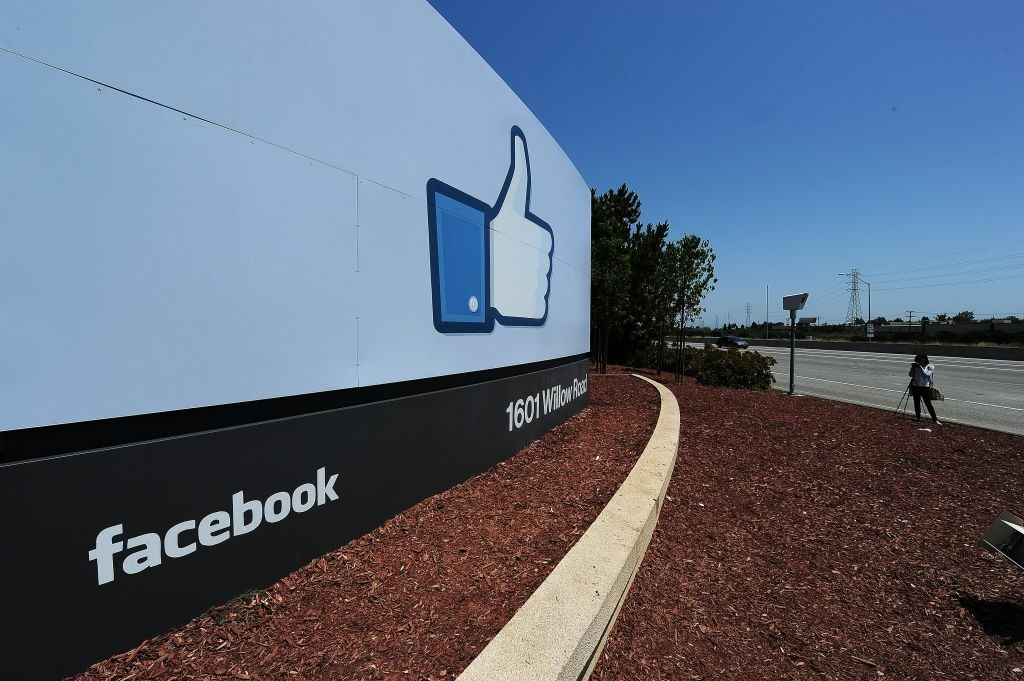 A woman shoots video of the sign at the entrance to the Facebook main campus in Menlo Park, California, May 15, 2012.