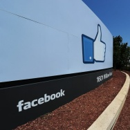 A woman shoots video of the sign at the entrance to the Facebook main campus in Menlo Park, California