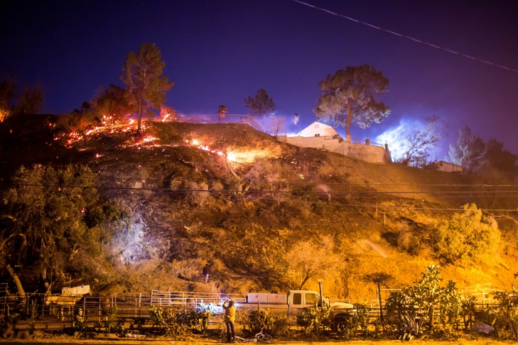 A resident watches as the Creek Fire burns along a hillside near homes in the Shadow Hills neighborhood of Los Angeles on Dec. 5, 2017.