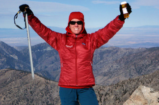 Cindy Abbott holds an ice axe and a medication bottle while on the summit of Mt. Baldy, Calif.