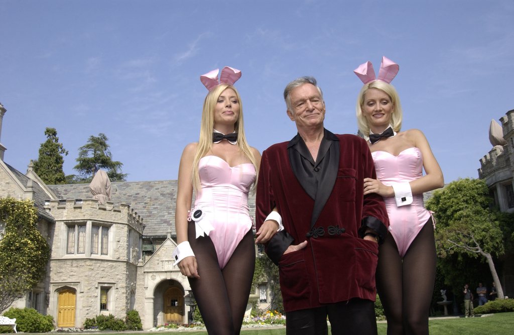 Playboy bunnies Sheila Levell ands Holly Madison flank Playboy founder Hugh Hefner in front of his Holmby Hills mansion.