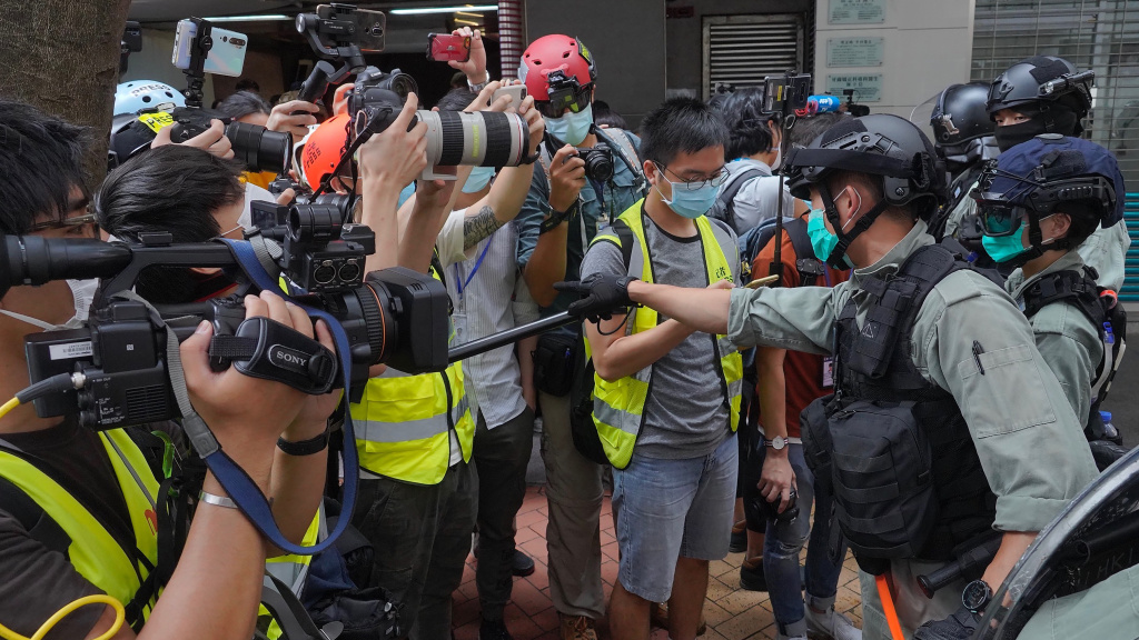 Riot police clear away media gathered in Hong Kong last week ahead of debate on a bill that would criminalize abuse of the Chinese national anthem. China has accused the U.S. of