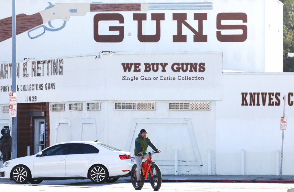 A cyclist rides past the Martin B. Retting, Inc. guns store as the coronavirus pandemic continues on March 24, 2020 in Culver City, California. L.A.