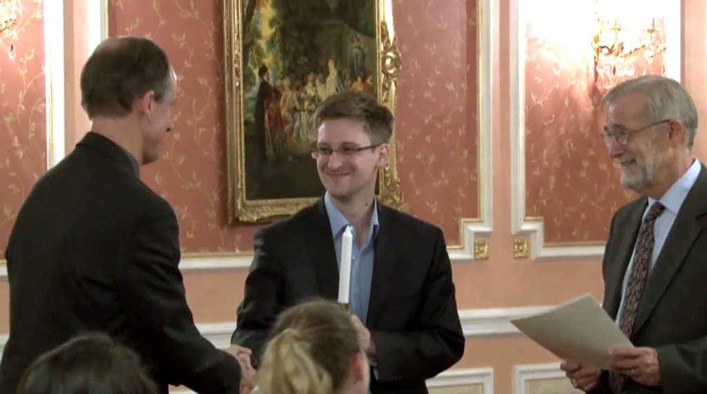 In this image made from video released by WikiLeaks on Oct. 11, 2013, former National Security Agency systems analyst Edward Snowden, center, receives the Sam Adams Award in Moscow, Russia. At right in the photo is Raymond McGovern, a former U.S. government official; at left is former NSA executive Thomas Drake. The latest revelation in documents released by Snowden shows that the NSA scooped up data from 60 million phone calls made in Spain over a four-week period in late 2012 and early 2013.
