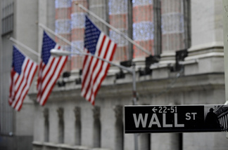 A street sign stands on Wall Street in front of the New York Stock Exchange.