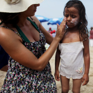 An Israeli woman rubs sunscreen on a  Palestinian girl from the West Bank village of Jahalin as they spend the day at the beach on August 2, 2010 in Bat Yam, Israel.