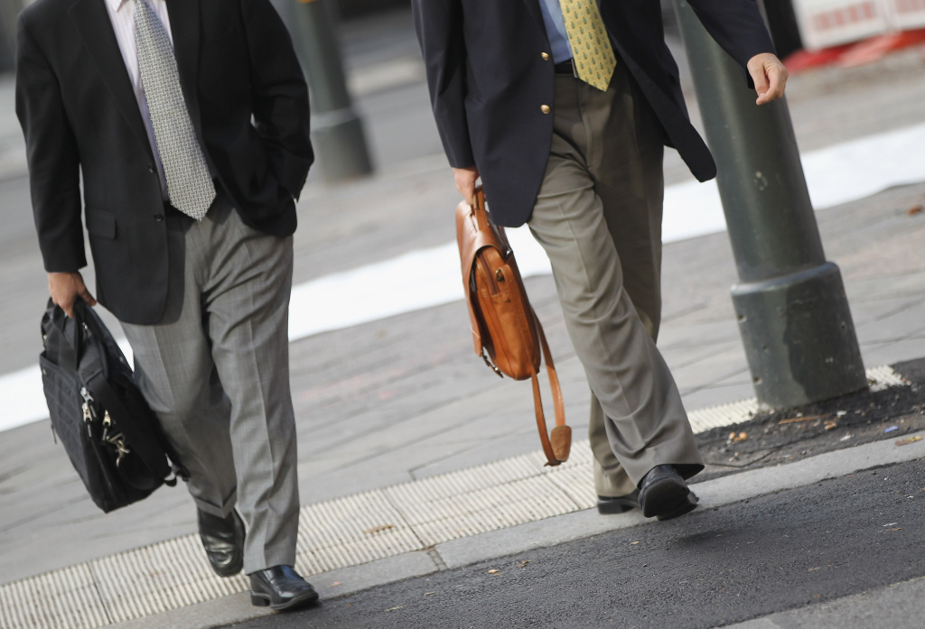 Men carrying briefcases walk at the intersection of Friedrichstrasse and Unter den Linden in Mitte district on October 12, 2011 in Berlin, Germany.