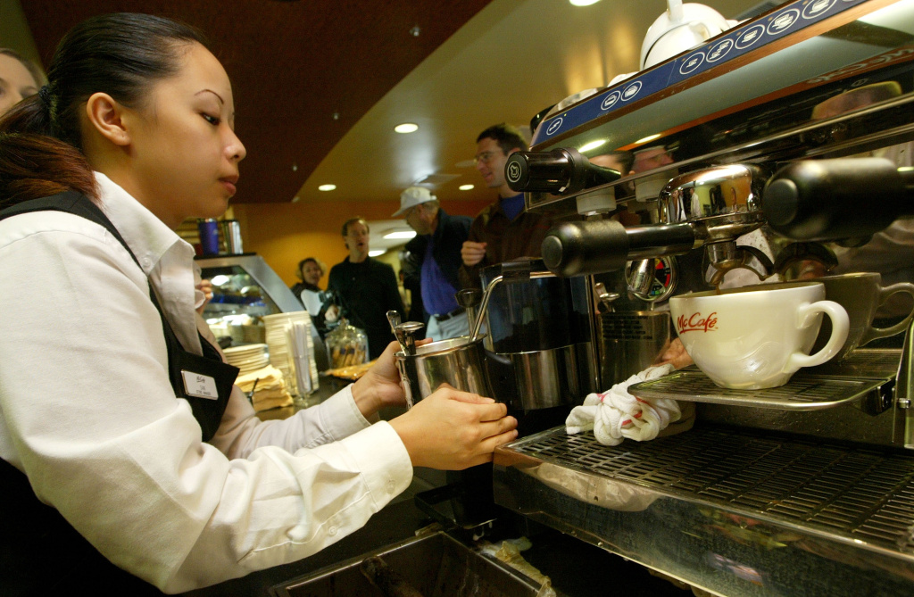 Samantha Vang steams milk for a coffee drink at the opening of a new McCafe coffeehouse December 3, 2003 in Mountain View, California.