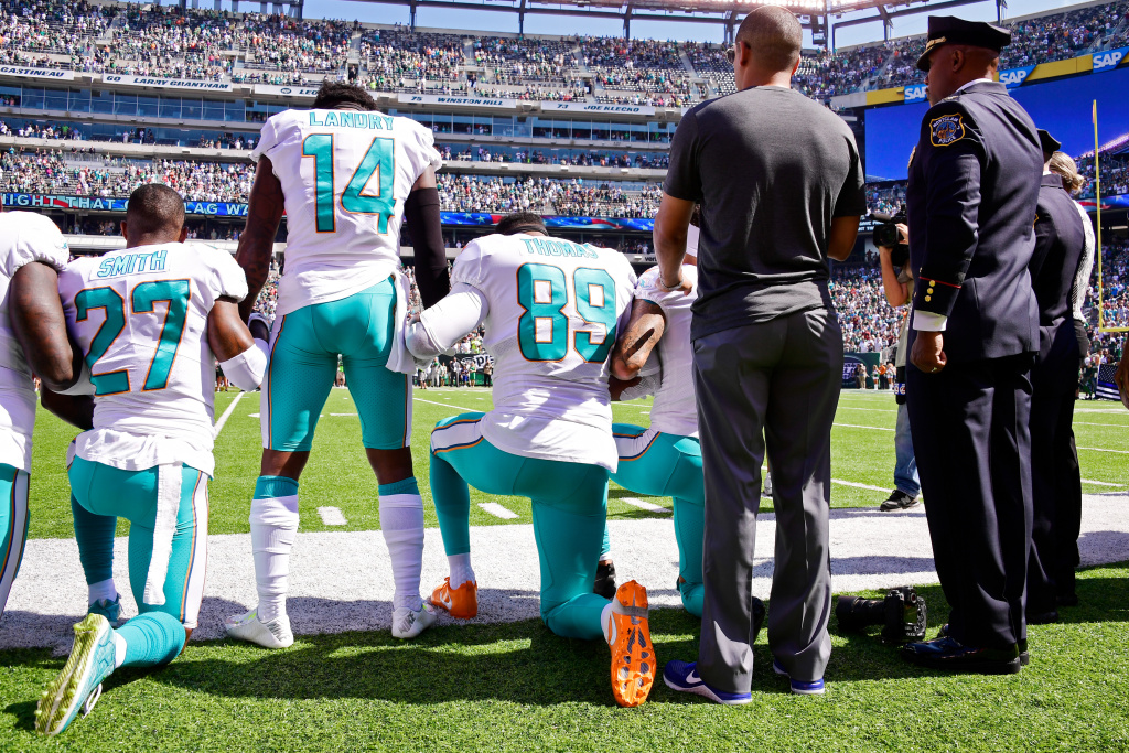 Maurice Smith and Julius Thomas kneel of the Miami Dolphins kneel during the national anthem prior to a game against the New York Jets on September 24, 2017 in East Rutherford, New Jersey.