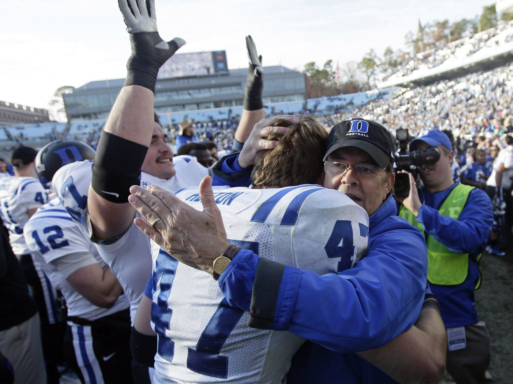 Duke coach David Cutcliffe hugs David Helton (47) following Duke's 27-25 win over North Carolina on Nov. 30.