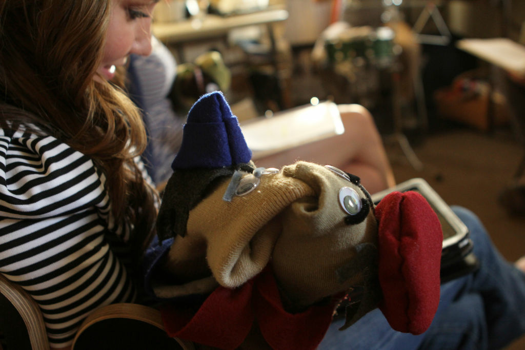 Actress Alicyn Packard holds her sock puppet characters as she studies the script to the pilot episode of