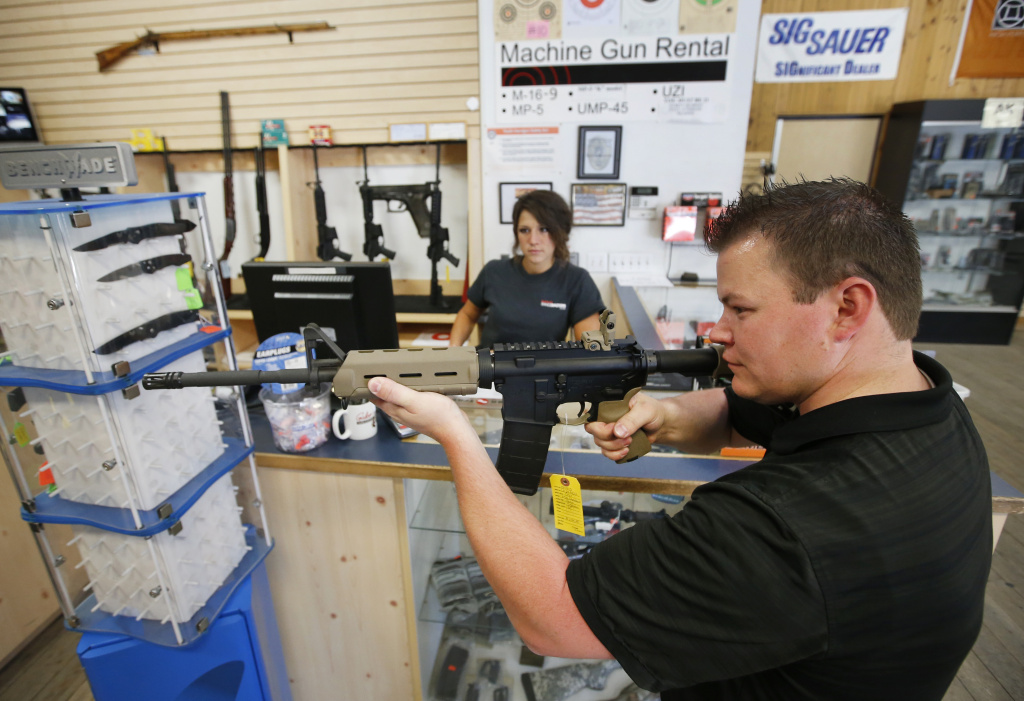 Courtney Manwaring, (L) shows an AR-15 semi-automatic gun to David Barker (R) at Action Target in Springville, Utah.