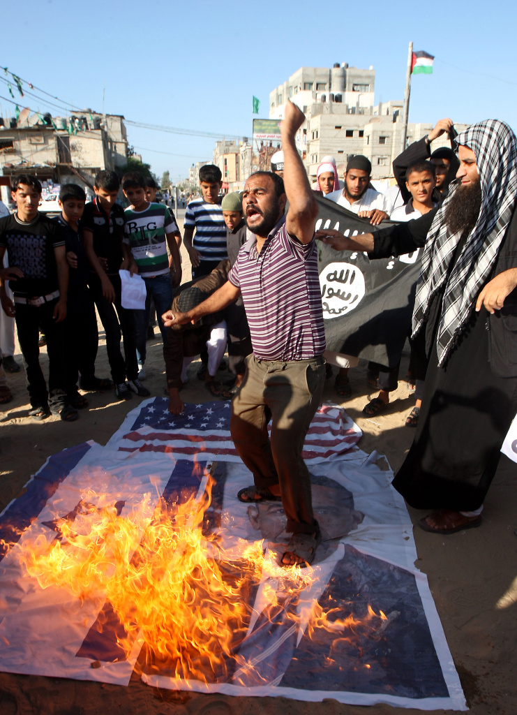 A Palestinian Salafist shouts slogans as protesters burn a picture of US President Barack Obama along with Israeli and US flags during a demonstration against an amateur film mocking Islam in Rafah in the southern Gaza Strip on September 14, 2012. Anti-US protests by crowds whipped into fury by a film that mocks Islam erupted across the Muslim world, as violence exploded in Sudan, Lebanon, Tunisia and Yemen leaving five dead and dozens injured.