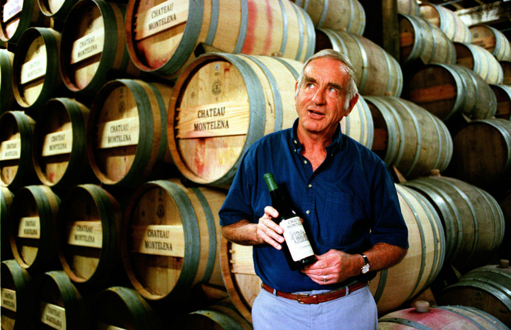 Jim Barrett, owner of Chateau Montelena, holds a bottle of the 1973 Chardonnay that won the 1976 Paris Tasting, while standing by barrels in the winery's cellar in Calistoga, Calif.  Barrett, a vintner whose superb wines put California on the international map, died Thursday, March 14, 2013. He was 86.  Barrett's 1973 Chateau Montelena Chardonnay beat the French at the Judgment of Paris in 1976, and helped transform California's wine industry into the powerhouse it is today.