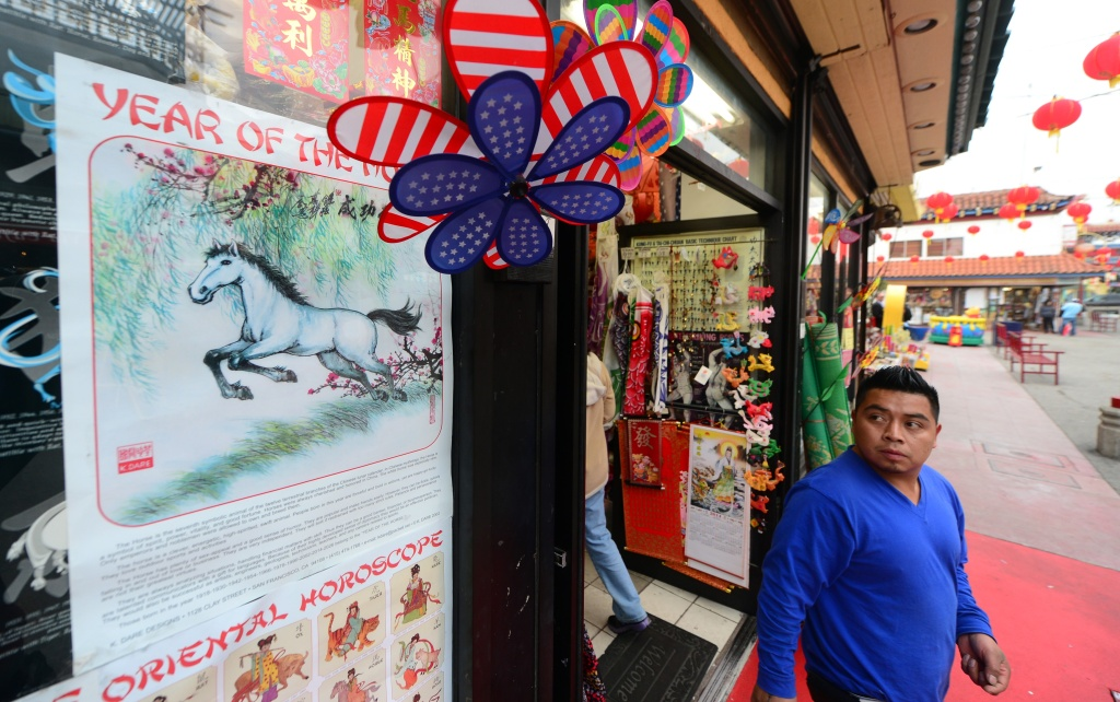 A man steps out of a shop selling curios and trinkets looking toward a Year of the Horse on the shopfront window in Chinatown's Central Plaza in Los Angeles on January 30, 2014, on the eve of the Year of the Horse, or 4712 in the Chinese Calendar.