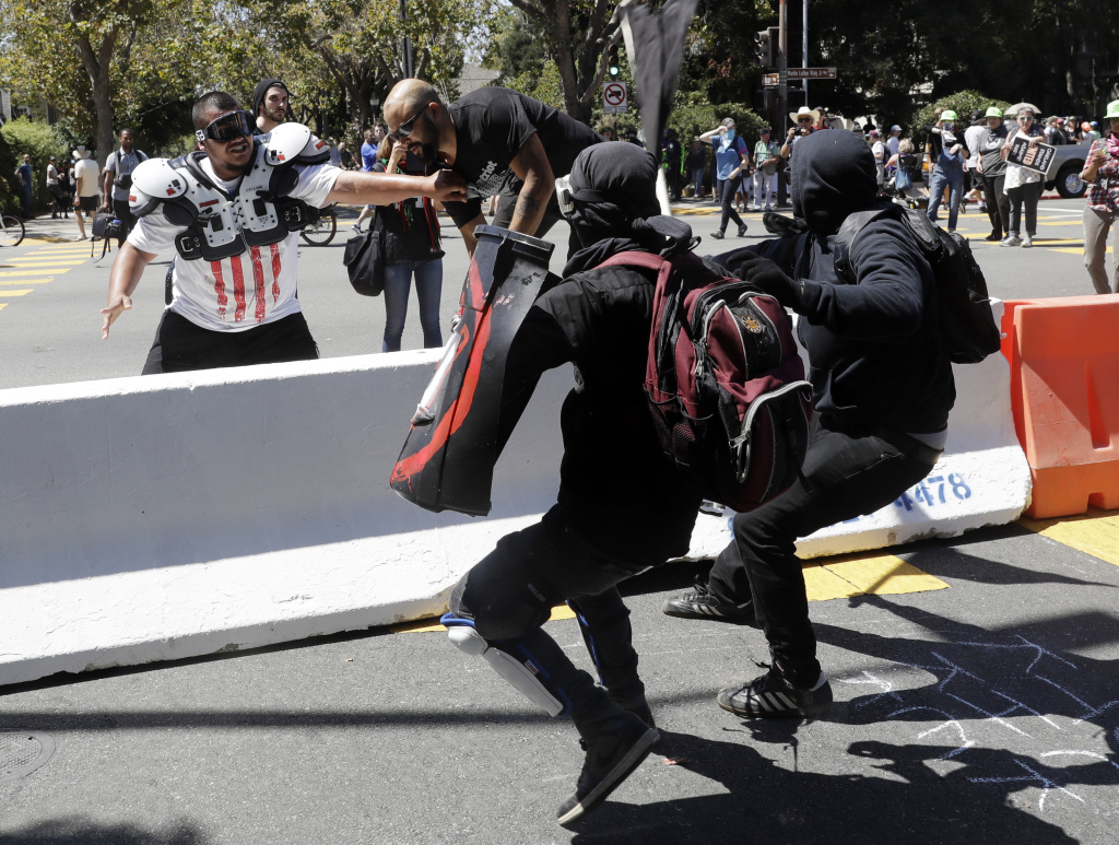 Demonstrator Joey Gibson, second from left, is chased by anti-fascists during a free speech rally Sunday, Aug. 27, 2017, in Berkeley, Calif. Several thousand people converged in Berkeley Sunday for a
