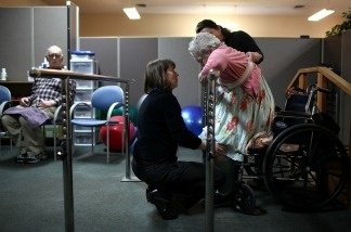 Physical therapist helps woman stand up at Lifelong Medical Marin Adult Day Health Care Center on February 10, 2011 in Novato, California; the center would be forced to close if Gov. Brown's proposed budget cuts were approved.