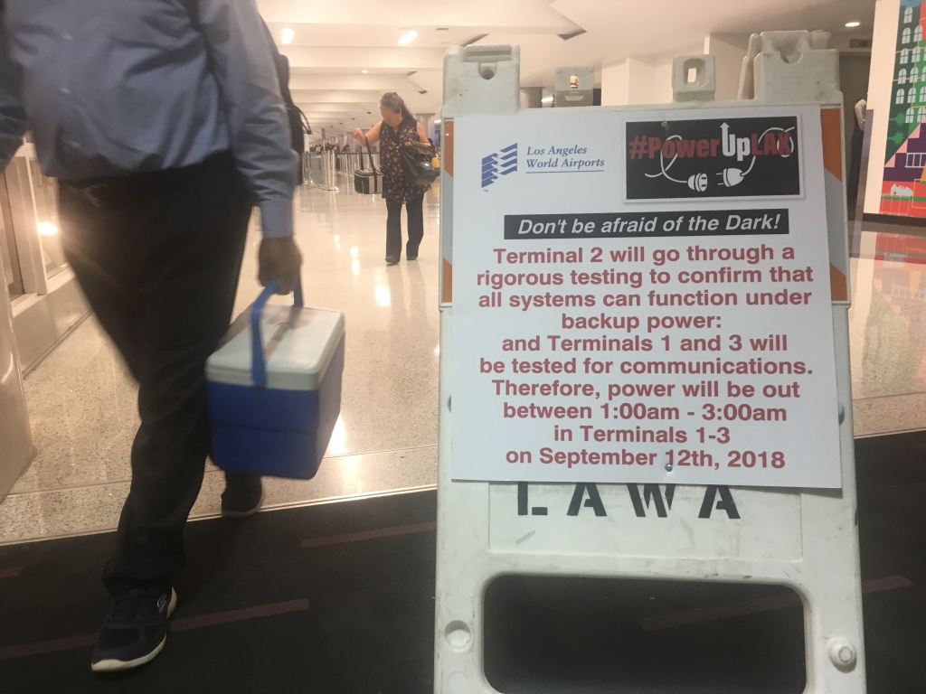 A worker carrying a cooler walks by a placard informing passengers of a power systems test at LAX Terminal 2 early Sept. 12, 2018.
