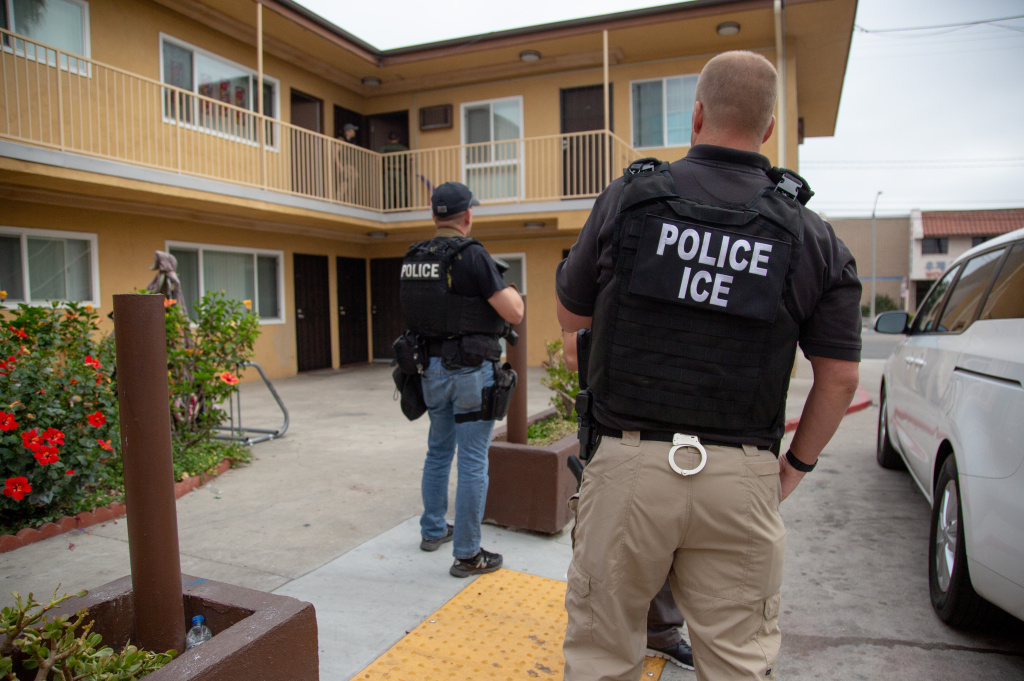 Immigration and Customs Enforcement agents talk with a suspect who is taking care of a child in an apartment building during a multi-day operation on Sunday, June 10, 2018 in Fullerton, California.